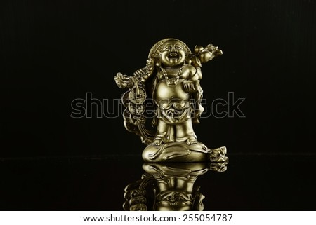 Chinese statuette on black background  - stock photo