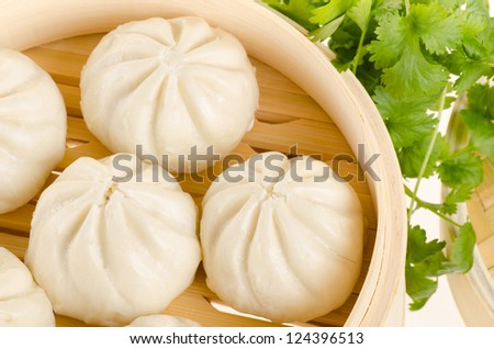 Chinese steamed buns in bamboo steamer basket with cilantro on w - stock photo