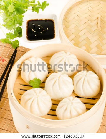 Chinese steamed buns in bamboo steamer basket with cilantro, soy sauce over the bamboo mat - stock photo