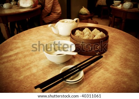 Chinese steamed dimsum in bamboo containers traditional cuisine with tea - stock photo