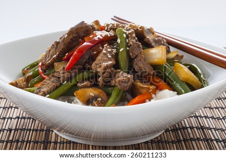 Chinese style beef and green bean stir-fry on white rice.  - stock photo