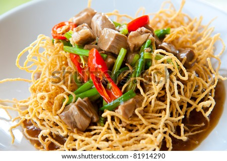Chinese style deep fried yellow noodles with pork, chili, vegetables and soup - stock photo