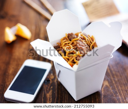 chinese take out with smart phone on table and menu - stock photo