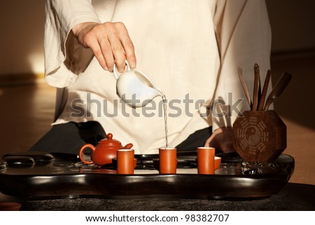 Chinese tea ceremony is perfomed by tea master in kimono - stock photo
