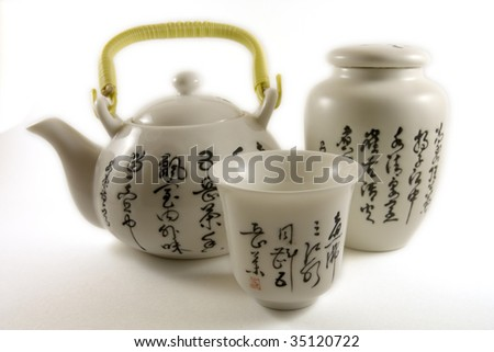 Chinese tea pot with tea cup and tea leaf container with chinese writings - stock photo