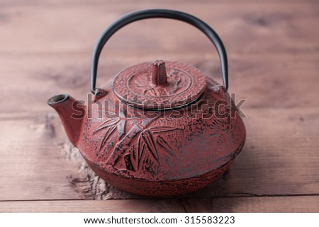 chinese teapot on wooden table - stock photo