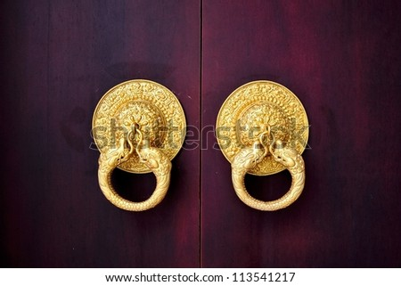 Chinese Traditional Crimson Wooden Door with Golden Knocker - stock photo