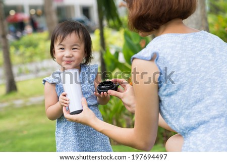 Chinese woman giving her daughter a glass of milk outdoors - stock photo