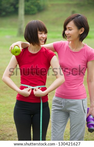Chinese Woman measuring shape of beautiful waist with smile for Healthy lifestyles concept with nature green background - stock photo