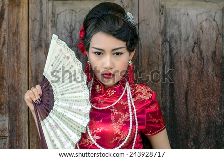 Chinese woman red dress traditional cheongsam ,close up portrait with old wood door - stock photo