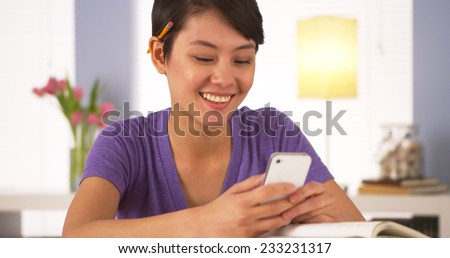 Chinese woman texting classmate on smartphone - stock photo