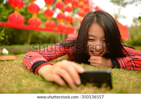 Chinese woman use smartphone in the park during chinese new year - stock photo