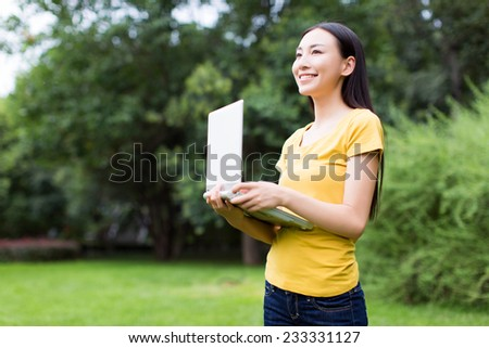 chinese woman working on her laptop in the park - stock photo