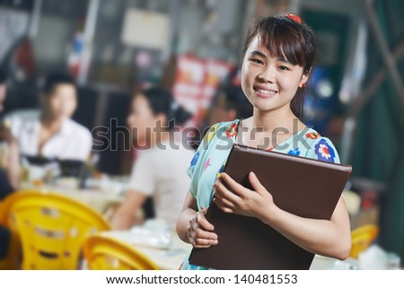 Chinese young waitress girl of street restaurant in china with menu waiting an order - stock photo
