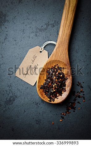 Chipotle chili flakes on a wooden spoon - stock photo