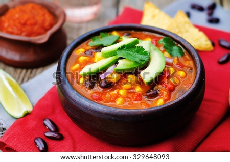 Chipotle red bean tortilla soup on a dark wood background. toning. selective focus - stock photo