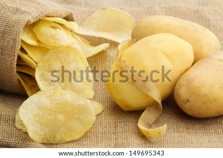 chips and peeled potato on a jute texture - stock photo