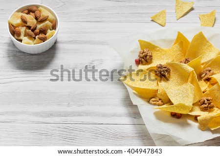 Chips, cheese and nuts on a wooden background - stock photo