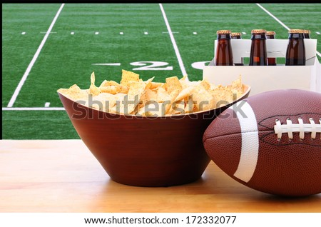 Chips, football and Six Pack of Beer on a table in front of a big screen TV with a Football field. Great for Super Bowl themed projects. Horizontal format. - stock photo