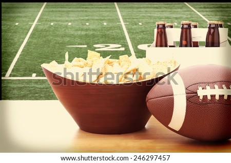 Chips, football and Six Pack of Beer on a table in front of a big screen TV with a Football field. Great for Super Bowl themed projects. Horizontal format with instagram effect applied. - stock photo