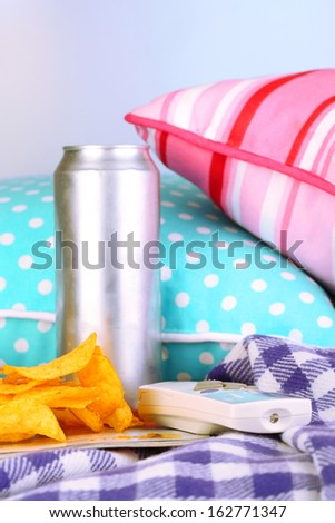 Chips in bowl, beer and TV remote on plaid on pillows background - stock photo