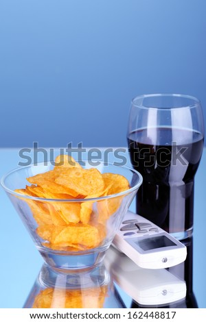 Chips in bowl, cola and TV remote on blue background - stock photo