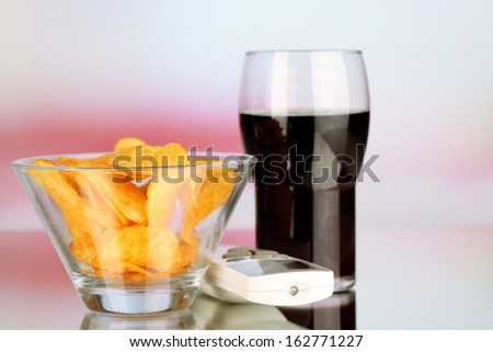 Chips in bowl, cola and TV remote on bright background - stock photo