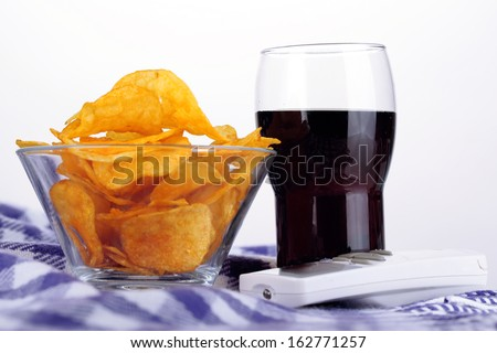 Chips in bowl, cola and TV remote on plaid isolated on white - stock photo