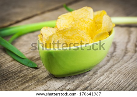 Chips with spring onion on  old wooden boards - stock photo