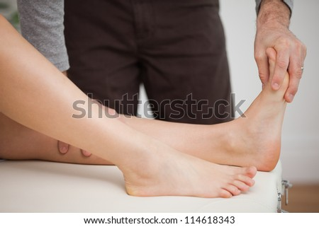 Chiropodist touching the foot of a patient in a room - stock photo
