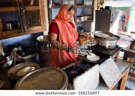 CHITRAKOOT, INDIA - DEC 28: Senior indian lady in sari dress cook national bread in the small street cafe on December 28, 2012. Population of Chitrakoot is 22,294. By the legend, Lord Rama lived here  - stock photo
