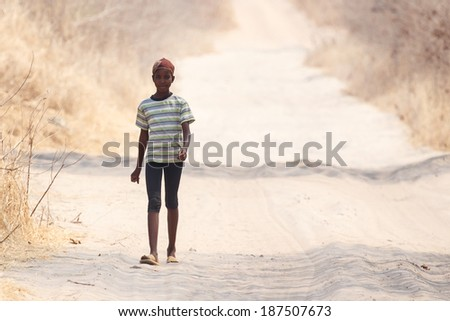 CHOBE, BOTSWANA - OCTOBER 5 2013: Poor African child wanders through the desert like Chobe National Park. This year was declared as a drought year by the government in Botswana, Africa - stock photo