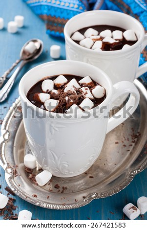 Chocolate almond milk with chocolate and marshmallow on blue background. Selective focus - stock photo
