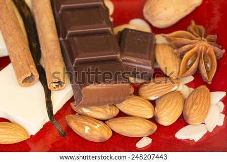 Chocolate, almonds and spices on a red ceramic background - stock photo