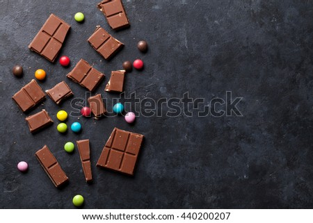 Chocolate and candy sweets on dark stone background. Top view with copy space - stock photo