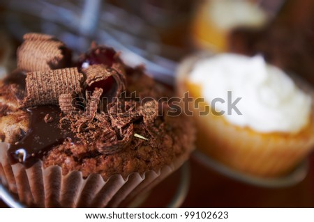 Chocolate and cream filled cupcakes with glazed cherries and chocolate shavings on a display stand. Shallow Depth of field with focus on the chocolate cupcake - stock photo
