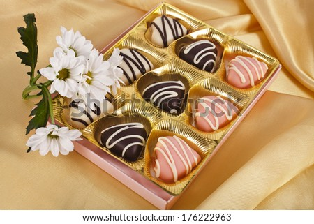chocolate and marchpane hearts candies on golden silk textured cloth background  - stock photo