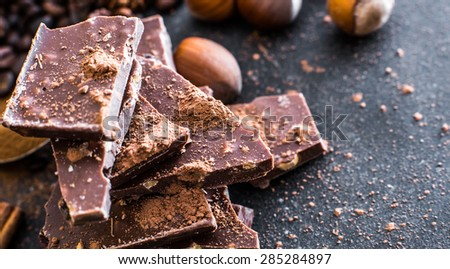 Chocolate and nuts on a black table with a worn surface - stock photo