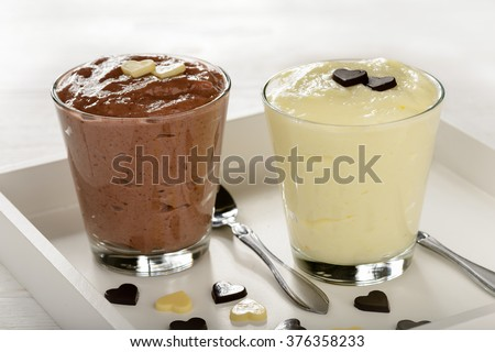 Chocolate and vanilla mousse decorated with chocolate hearts on wooden tray. - stock photo