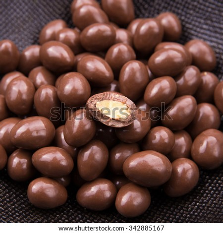 Chocolate ball candy smarties on black background with nuts inside - stock photo