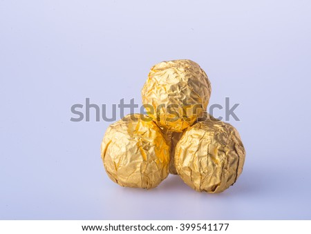 Chocolate ball in a gold foil paper on a background - stock photo
