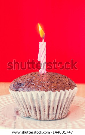 Chocolate banana cupcake on red background (Process effect in vintage style on this photo) - stock photo