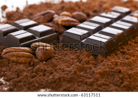 Chocolate bar broken in half with cocoa powder and nuts. - stock photo