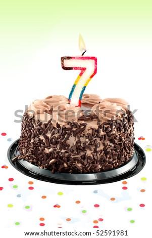 Chocolate birthday cake surrounded by confetti with lit candle for a seventh birthday or anniversary celebration - stock photo