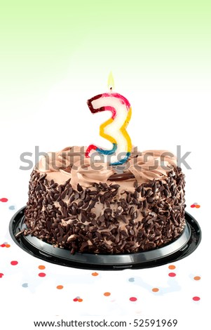Chocolate birthday cake surrounded by confetti with lit candle for a third birthday or anniversary celebration - stock photo