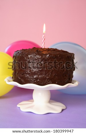 Chocolate birthday cake with one lit candle  - stock photo