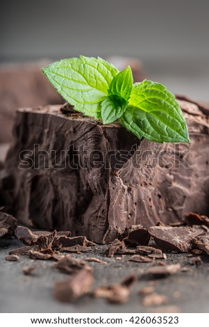 Chocolate. Black chocolate. A few cubes / blocks of black chocolate with mint leaves. Chocolate slabs spilled from grated chockolate powder. - stock photo