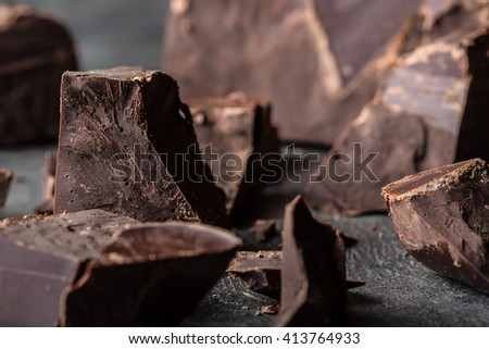 Chocolate. Black chocolate. A few cubes of black chocolate. Chocolate chunks. Chocolate bar pieces. - stock photo