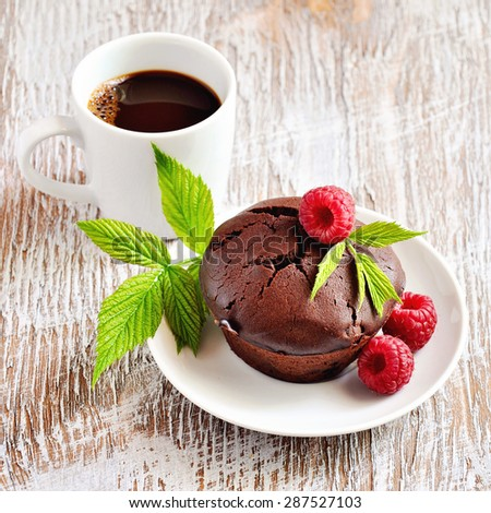 Chocolate brown muffins with fresh raspberries and a cup of espresso coffee for breakfast on wooden table. Selective focus. - stock photo