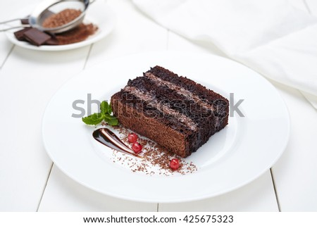 Chocolate brownie cake with cocoa cream and berry sauce in white plate. Delicious pastry dessert. - stock photo